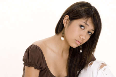 A pretty young asian woman sits and thinks photo