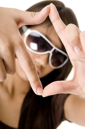 A young woman frames herself with fingers and thumbs photo