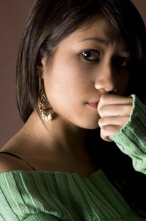 sidelight: A moody portrait of a young woman in green jumper Stock Photo