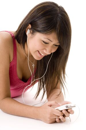 portable mp3 player: A pretty young woman in a pink top listens to music on her portable mp3 player