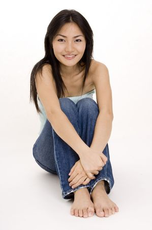 demure: A beautiful young asian woman sitting on the floor Stock Photo