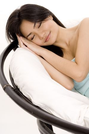 comfortable chair: A pretty young asian woman takes a nap in a big comfortable chair