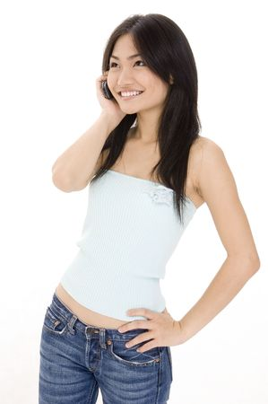 demure: A pretty young asian woman listens on the phone Stock Photo