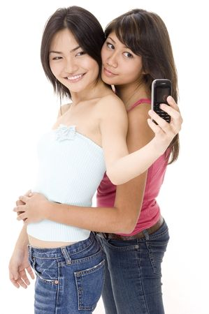 demure: Two pretty young women take their picture using their phone