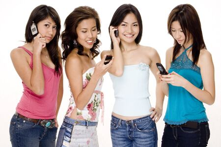 Four attractive young women using their phones (cellphones/mobiles) Stock Photo - 297106