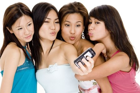Four attractive young women pucker-up for the camera on the phone photo
