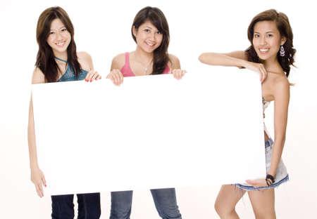 trio: Tres mujeres j�venes atractivas llevan a cabo una muestra en blanco grande Foto de archivo