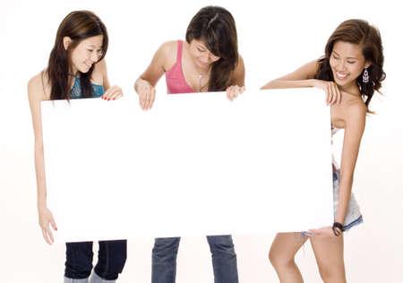 trio: Tres mujeres j�venes atractivas miran la muestra en blanco grande que est�n llevando a cabo
