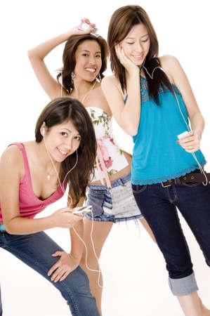 trio: Tres mujeres atractivas j�venes asian escuchar m�sica en dispositivos port�tiles de m�sica