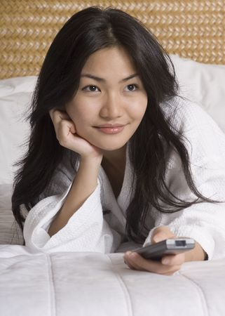A pretty young asian woman lies on the hotel bed with remote control (shallow depth of field) photo