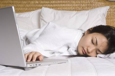 doze: A young woman falls asleep next to her laptop computer