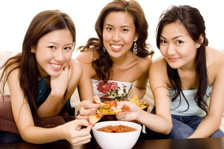 chips and salsa: Three pretty asian women eating nachos and salsa dip