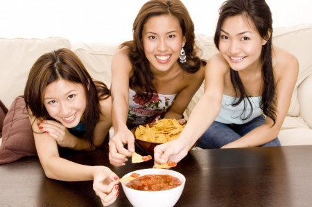 Three attractive asian women eating chips on the sofa photo
