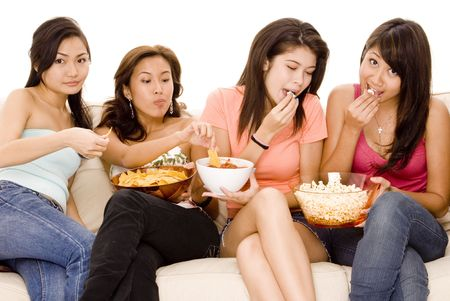 chips and salsa: Four pretty young asian women sitting on a sofa with popcorn and nachos