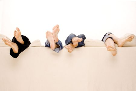 Four pairs of feet hang over the back of a beige sofa photo