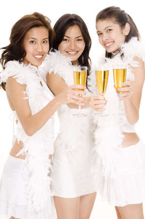 Three attractive asian women in white drinking champagne photo
