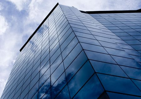 reflects: The blue sky reflects in the glass of a skyscraper in Singapore