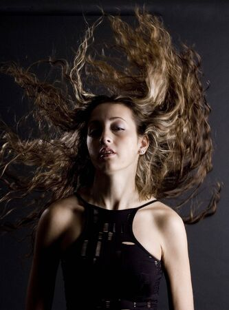A woman flicks her amazing hair above her head photo