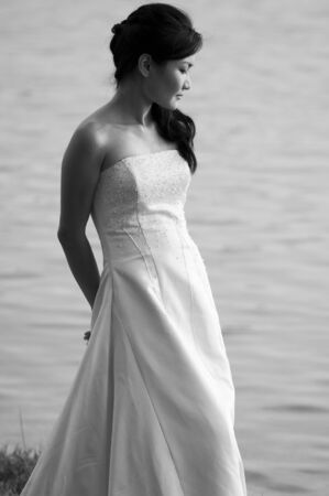A black and white shot of a beautiful asian bride shot outdoors by a lake
