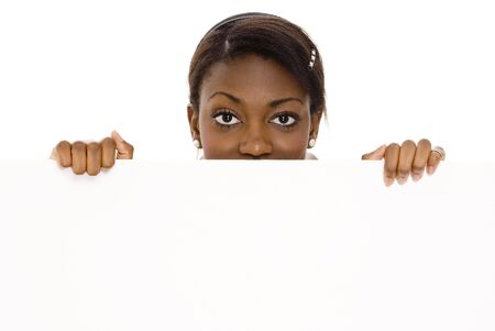 A young woman peers over a large blank white sign