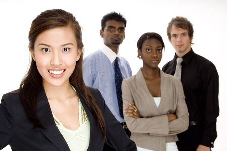 A smiling asian businesswoman (in focus) stands in front of her team (slightly off focus)
