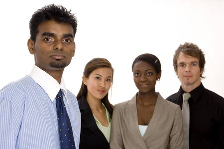 A tall businessman stands in front of a diverse group of business people