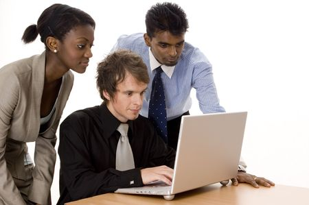 Three business men and women working on a laptop computer