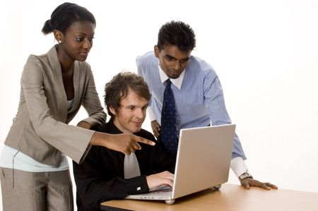 Three people working on a silver laptop computer
