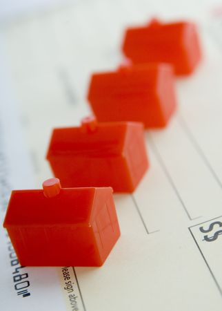 A row of red plastic houses lined up on a bank cheque (shallow depth of field used)