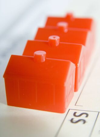 A row of red plastic houses next to the dollar sign on a cheque (shallow depth of field used)