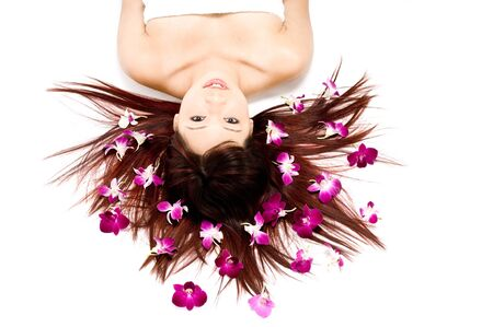 A young Asian woman lying on the floor with purple orchid flowers Stock Photo