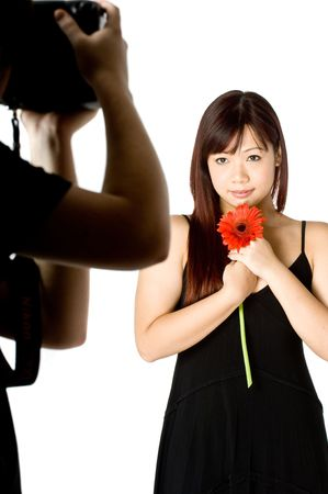 A young woman holding a red gerbera posing for a photographer in a studio photo