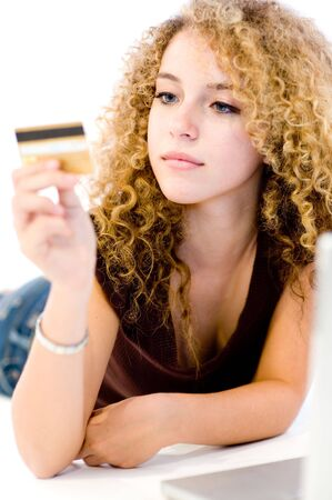 A young pretty woman with laptop computer and credit card on white background