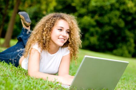 A young woman lying on the grass with laptop computer photo