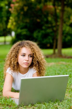 A young attractive woman using laptop in the park photo