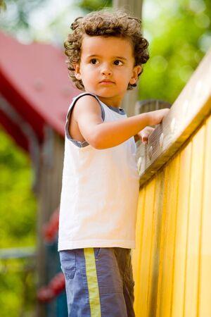 climbing frame: Un capretto giovane cute che gioca su una struttura rampicante in un parco