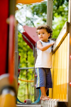 climbing frame: Un ragazzo giovane cute che giocano su un telaio di arrampicata in un parco
