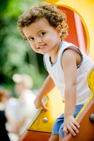 A cute young kid playing on a slide in a park Stock Photo