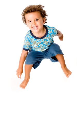 curly hair child: A cute young boy jumping in the air on white background Stock Photo