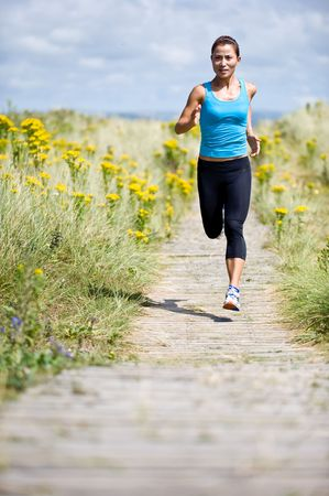 A young woman running in the countryside photo