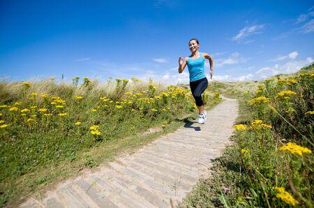 people jogging: Una joven mujer corriendo deportivo en el campo