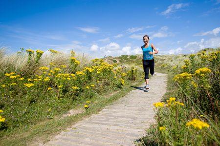 田舎で走っている若いスポーティな女性