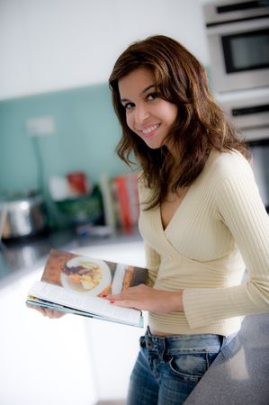 cookery: A young woman reading a cookery book in the kitchen Stock Photo
