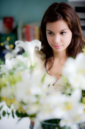 A pretty young woman arranging flowers in the kitchen Stock Photo - 3553297
