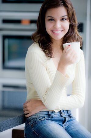 A young woman having coffee in the kitchen Stock Photo - 3597018