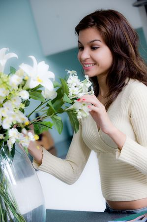 A pretty young woman arranging flowers in the kitchen photo