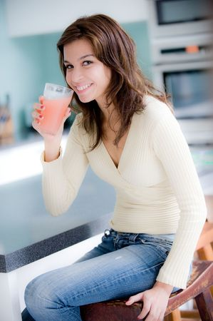A young woman having juice in the kitchen photo