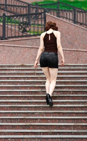 젊은 섹시한 여자는 대리석 단계를 올라