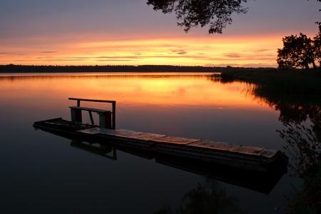 puesta de sol suave calmante en el estanque con puente de madera en primer plano