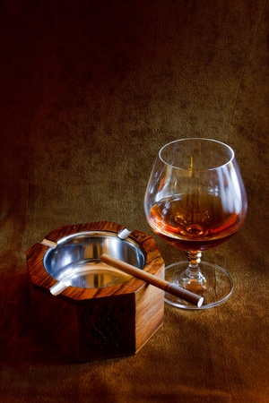 a glass of brandy and a wooden ashtray with a cigarette in the background of brown suede photo